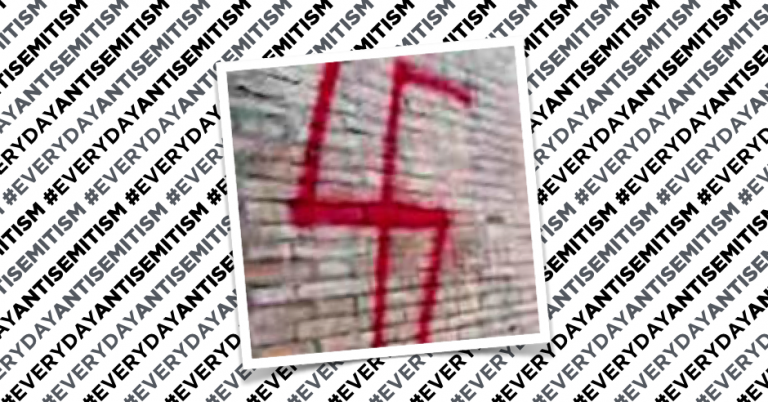 Bright red swastika painted on mediaeval tower in square in Rome