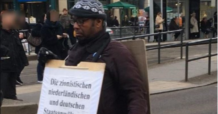 Man posing with antisemitic posters around Berlin
